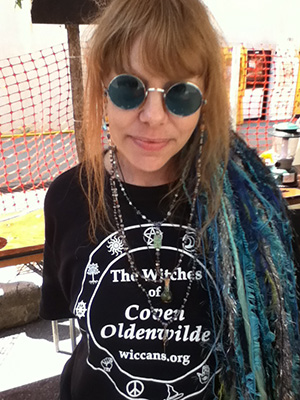 Lady Passion wearing her new terrarium talisman atop her Witches of Coven Oldenwilde T-shirt.