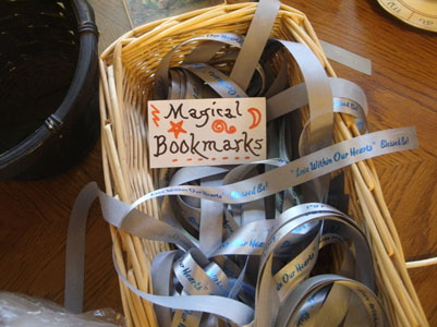 Decorated card, 'Magical Bookmarks', atop silver ribbons in basket