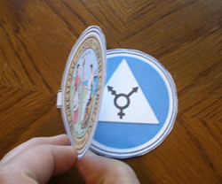 Folded lamen, top disc with state seal on outside held open to show bottom disc with blue restroom sign on inside