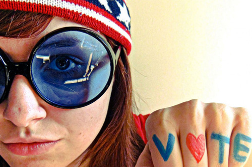 Young woman in blue sunglasses and patriotic ski cap shows fist with V Heart T E drawn on knuckles