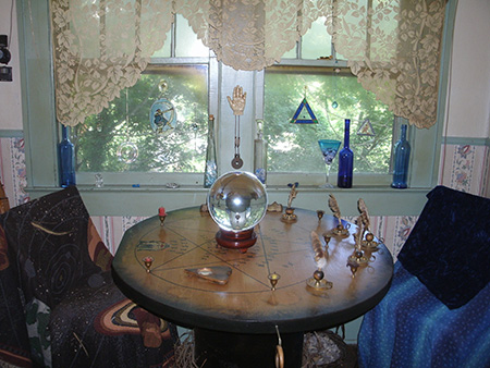 Clairvoyant psychic reader, divination specialist Lady Passion's 'div nook' for in-person psychic clairvoyant readings and divinations shows crystal ball and Tarot High Priestess symbol on a pentagram-inscribed Ouija table with two seats and a palmistry hand on the wall