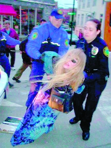 Lady Passion in blue tie-dye skirt having her arms twisted behind her back and being dragged down by two police officers